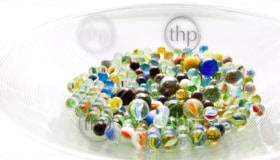 Brightly colored marbles in different shades in a bright glass bowl
