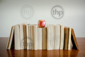 A row of books with an apple on top sits on a timber table with blank space behind