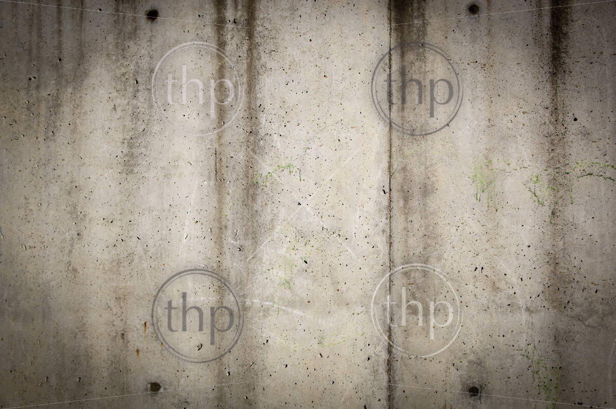 Tall concrete wall in rough, grunge style with stains and wear