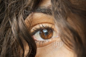 Beautiful woman's eye stares through hair hanging over her face