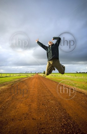 Adult male leaps high into the air with much excitement in a rural area