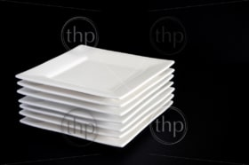 Contemporary square white plates stacked against a dark black background
