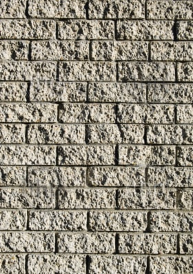 Grunge style brick wall with rough bricks in sunlight