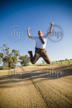 Businessman dressed in shirt and tie leaping high into the air with much excitement in a rural area