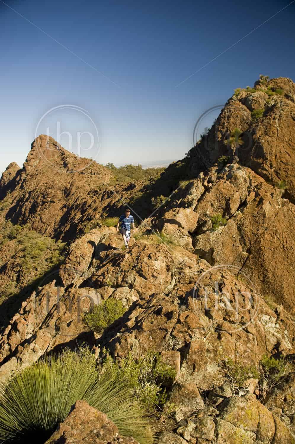A man walks along the ridgeline of red and orange coloured mountains in Mt Kaputar National Park, Australia