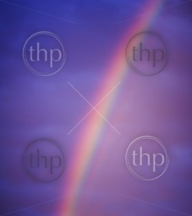 Rainbow in dark clouds emits purple, pink, yellow and green light