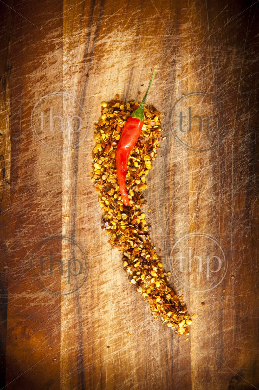 Red hot chilli concept - chilli sits atop chilli seeds shaped like a chilli