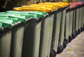 Row of large green wheelie bins for rubbish