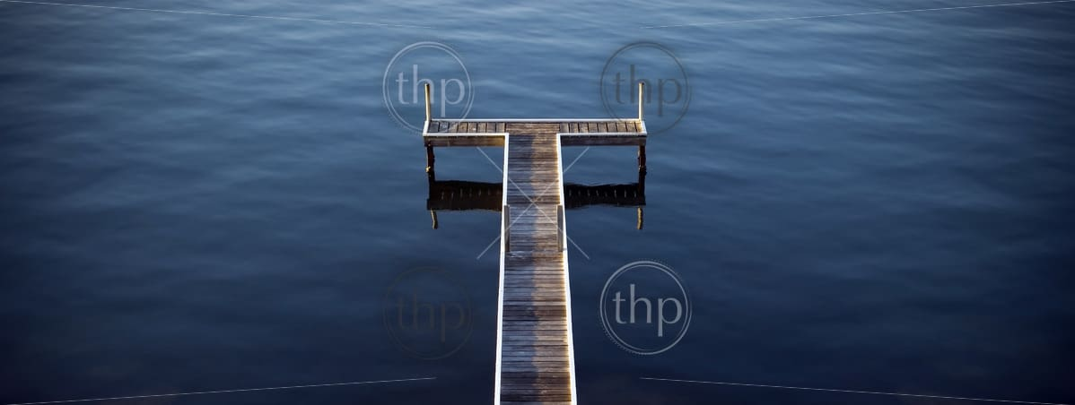 Wooden jetty stretches out into the ocean in perfect symmetry