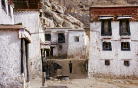 A lone figure walks between old buildings in the Buddhist Drepung Monastery, Tibet