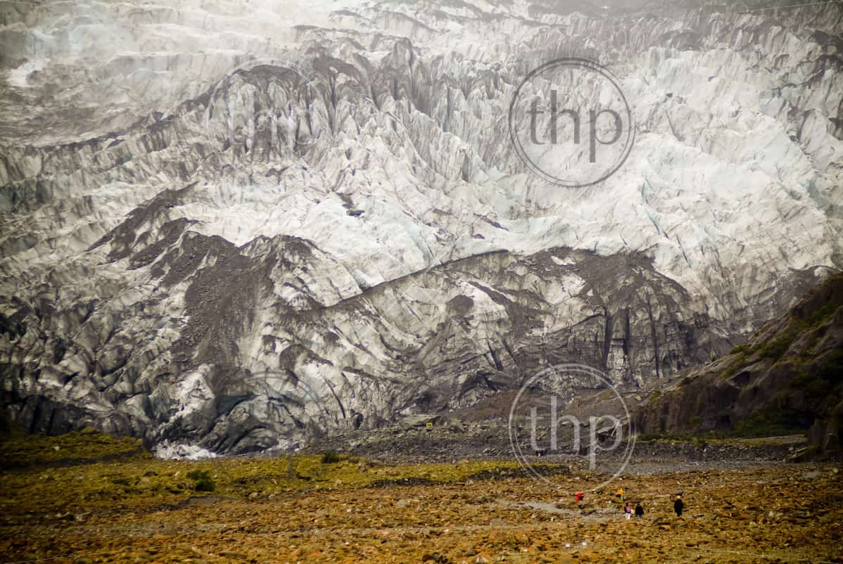 People walking in front of massive glacial wall