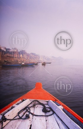 Rowing a wooden boat down the Ganges River, India at sunrise