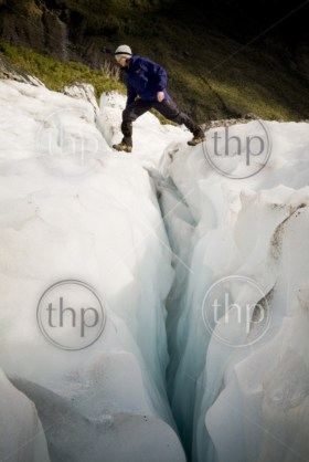 Man crosses a deep crevasse on a glacier