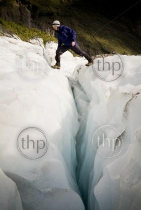 Man crosses a deep crevasse on a glacier