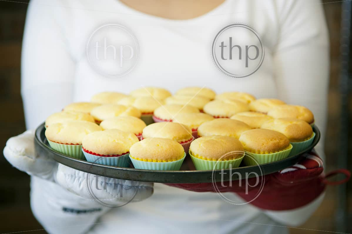 A woman holds out freshly baked cupcakes