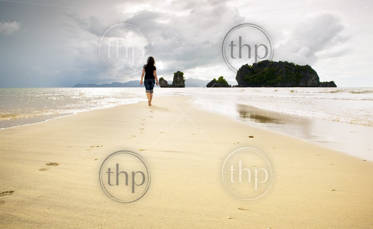 A young woman walks alone on a beach