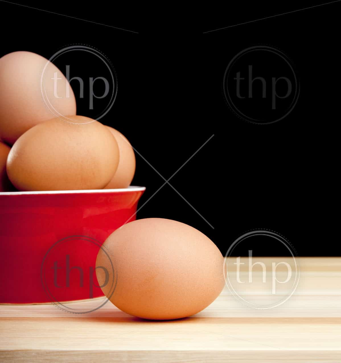 Eggs in a bowl and one on the bench isolated on black