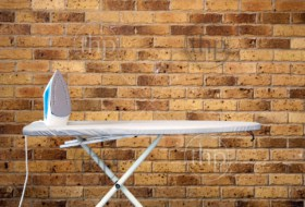 Retro style composition of an ironing board and iron against brick wall