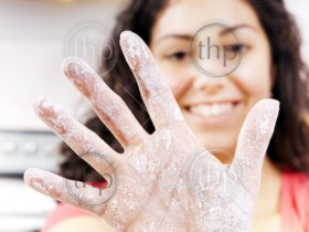 A smiling woman holds out a hand covered in flour while cooking