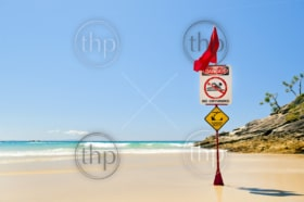 Classic Australian beach with warning flag from surf life savers