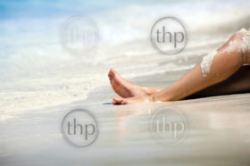 Womans legs on beautiful tropical beach with bright sand
