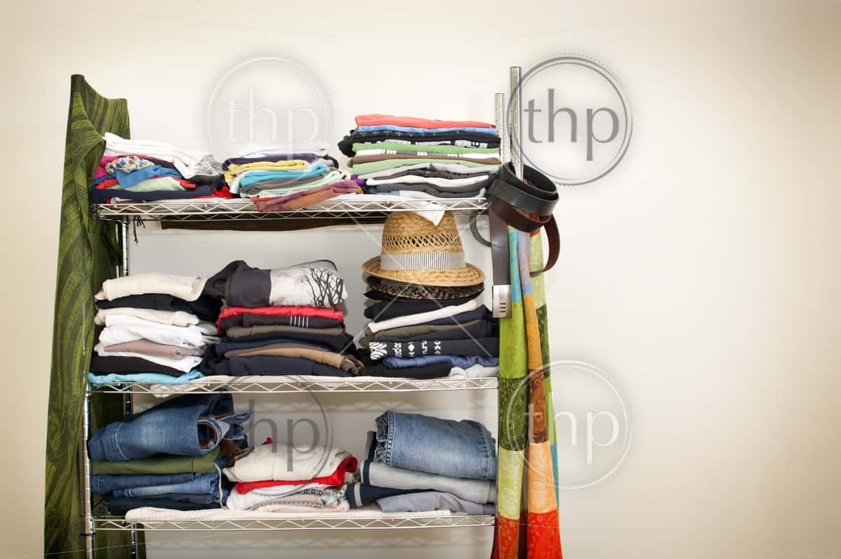 Clothes rack with stacked clothes for male and female, with jeans, tshirts, scarves, hats and more