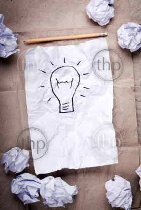 Crumpled paper with a lightbulb idea concept and crumpled paper attempts around it