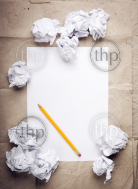 Writing concept - crumpled up paper wads with a sheet of white paper and pencil