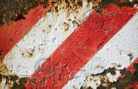 Grunge striped background of rusted metal and red and white painted stripes