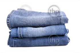 Blue jeans folded and stacked together, isolated on white