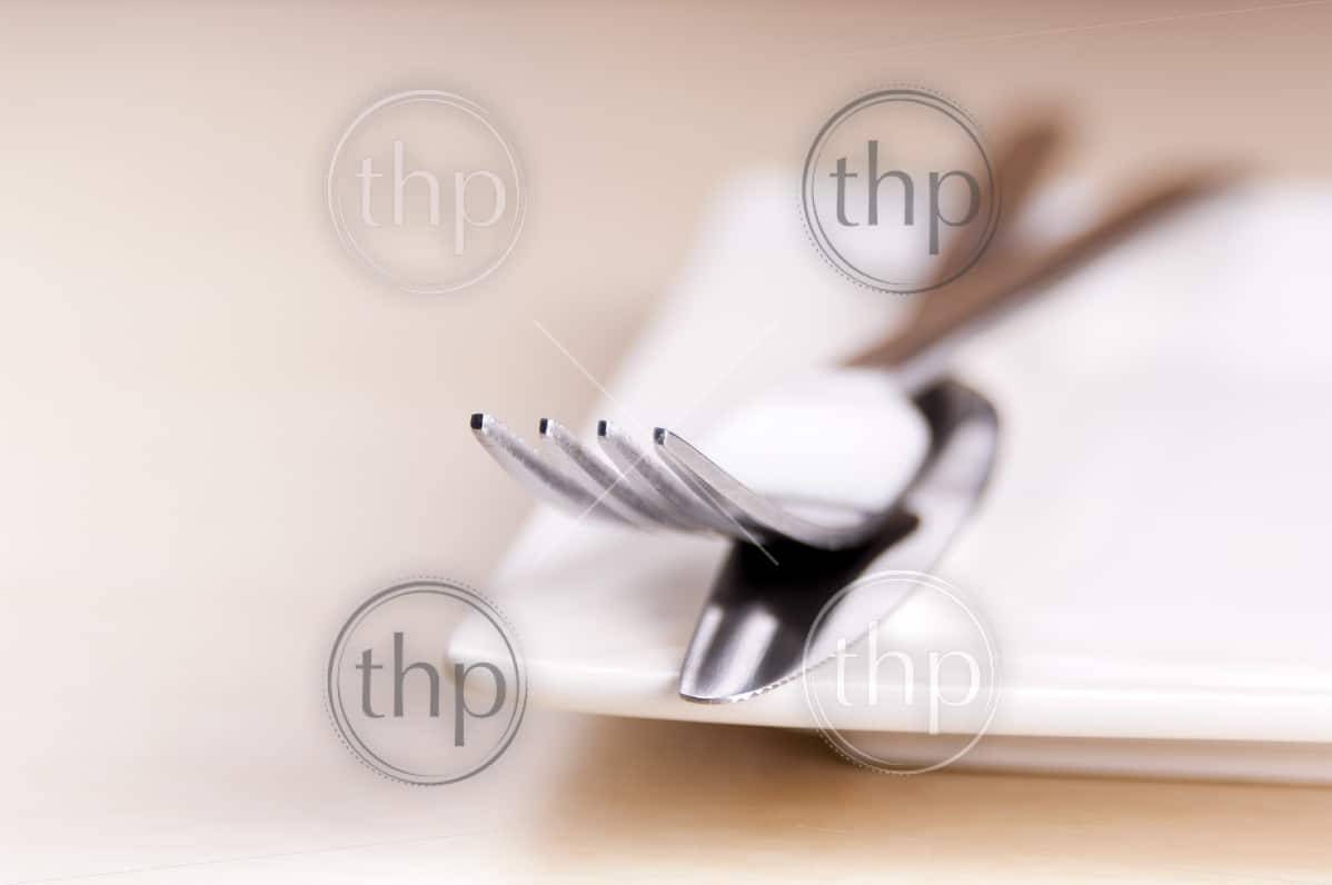 Knife and fork cutlery with a white place in very shallow focus
