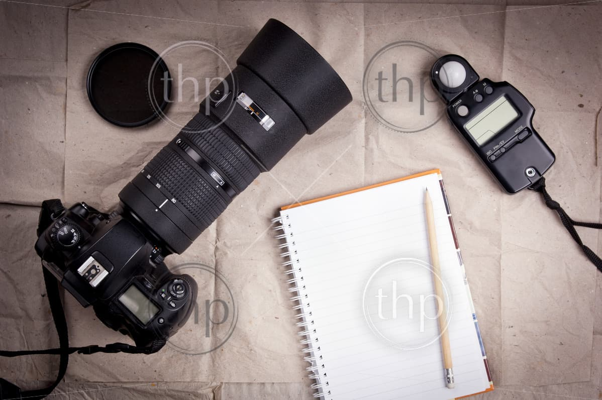 Photography equipment including a professional digital SLR camera and light meter with a blank notebook