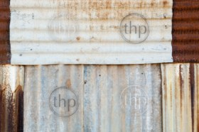Rusted metal background of corrugated iron and tin with rivets