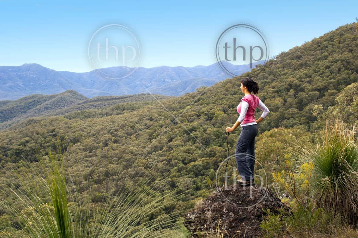 Single female hiker looks out at view in mountains with forest below her
