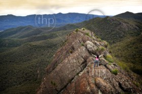 Single young woman looks out with determination on a mountain top