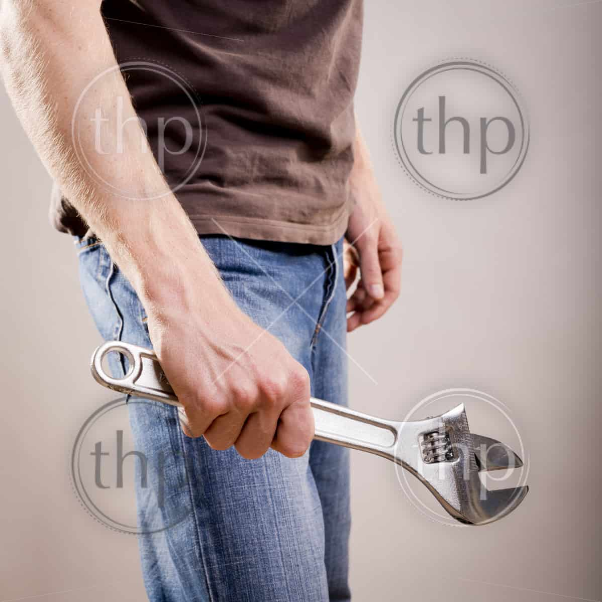 A young man dressed in casual clothes holds a large adjustable wrench or spanner