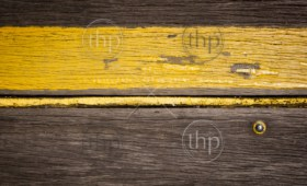 Yellow painted stripe on weathered wooden background