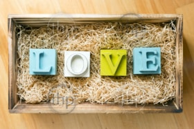 The word Love spelled out in big block letters in a wooden gift box filled with raffia