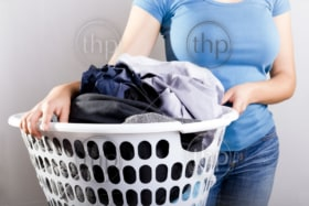 Casually dressed woman in blue shirt holding a basket full of dirty laundry needing washing