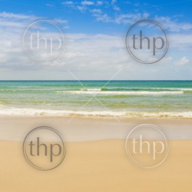 Beach with blue sky and blue water lapping the sand