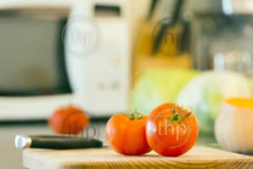 Preparing fresh food on the kitchen bench, with tomatoes, pumpkin and other vegetables in the background
