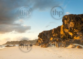 Large sea cliffs at sunrise with white sand and two motion blurred people fishing