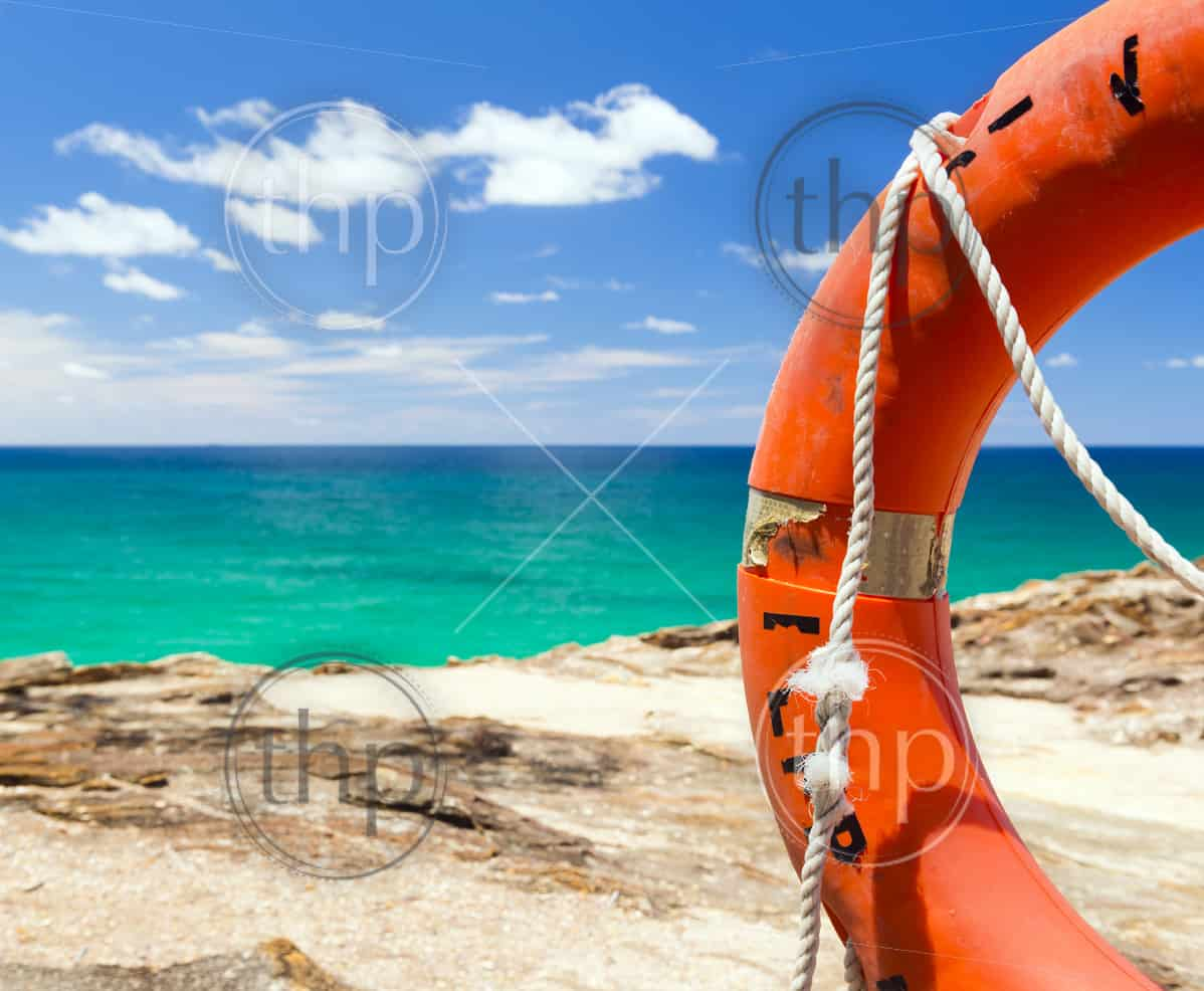 Bright orange surf live saving floating ring with the blue ocean behind
