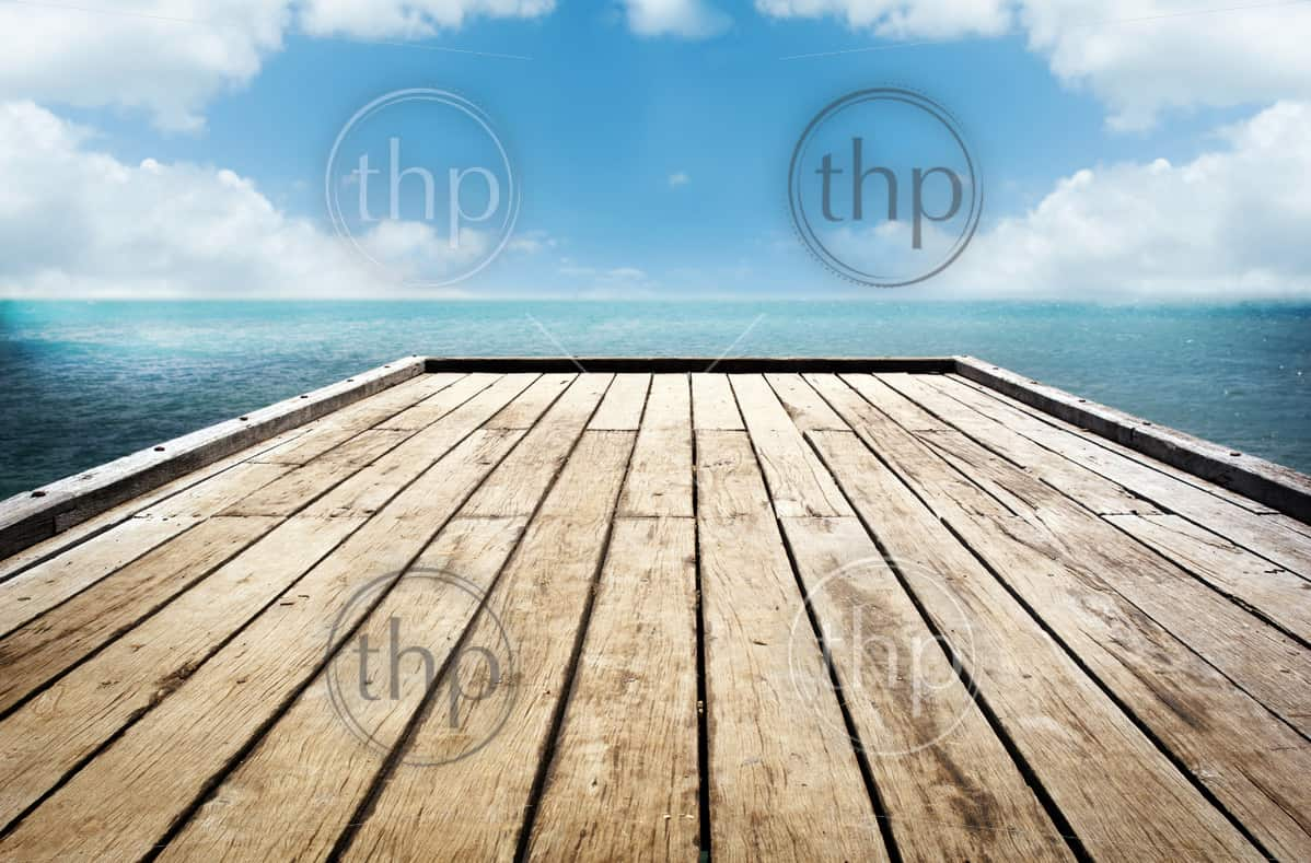 Bright wooden decking surface under a cloudy sky background