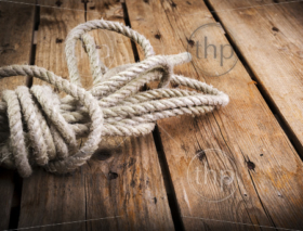 Old rope twisted and tied in a bundle on a rough wooden background