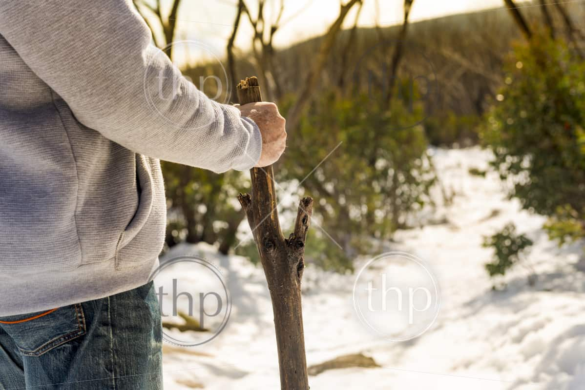 An senior aged retired man walking in the mountains for exercise with a walking stick