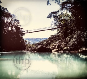 Vintage adventure photo with tilt shift focus of silhouette crossing wooden rope bridge with missing plank