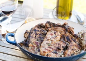 Barbequed lamb chops served up in a large white bowl in shallow focus