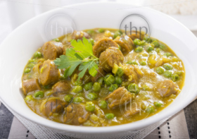Large bowl of curried sausages with peas and a side of rice