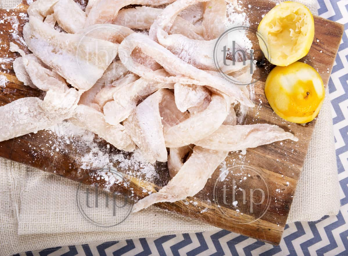 Fresh flathead fish fillets coated in flour ready for cooking with lemons